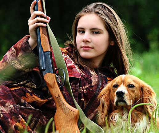 A picture of a girl, a gun, and a dog